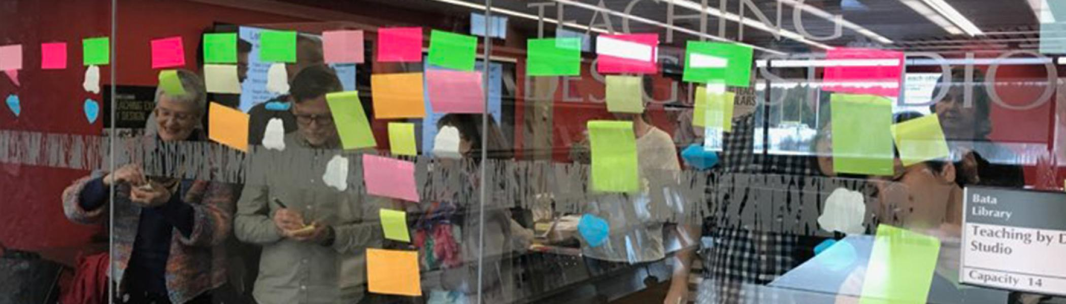 Photo from behind glass, while instructors do a sticky note activity in the opposing room.  Stickies posted to wall.