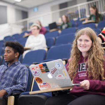 Student with laptop, sitting in a lecture hall smiling, surrounded by other students
