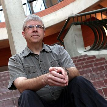Image of Rob Loney sitting on steps looking down at camera in the Science Complex