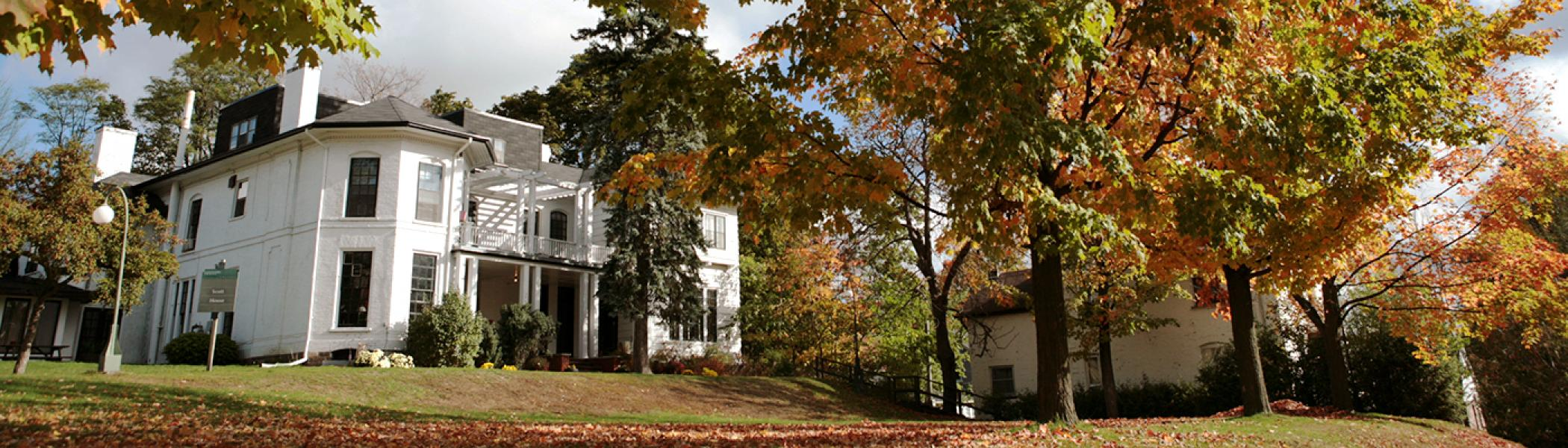 Traill College main white building on the hill in the fall leaves