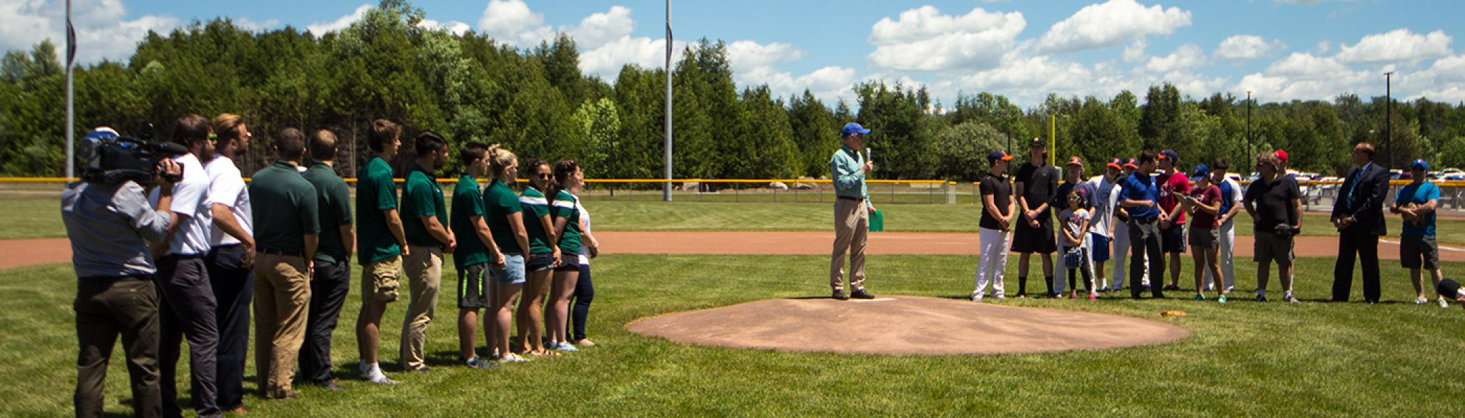 Dr. Leo Groarke standing on a baseball mound talking to a group of people