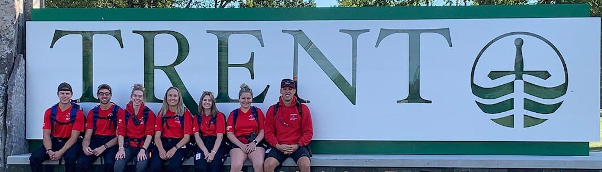 Students sitting alongside the Trent University entrance sign.