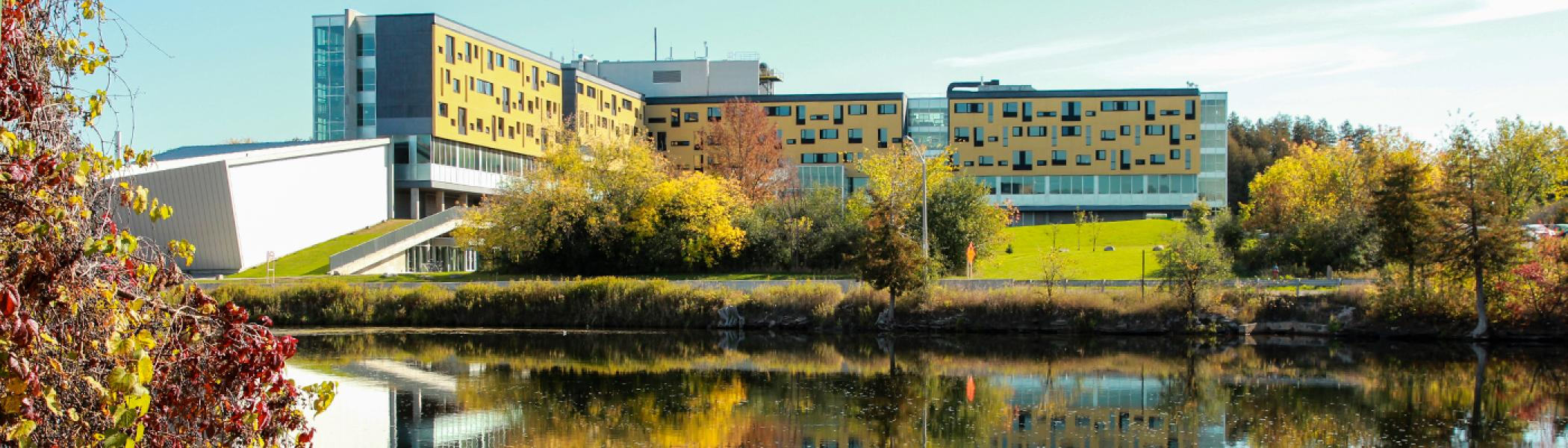 Exterior view of Gzowski College in the afternoon fall sun from across the Otonabee River