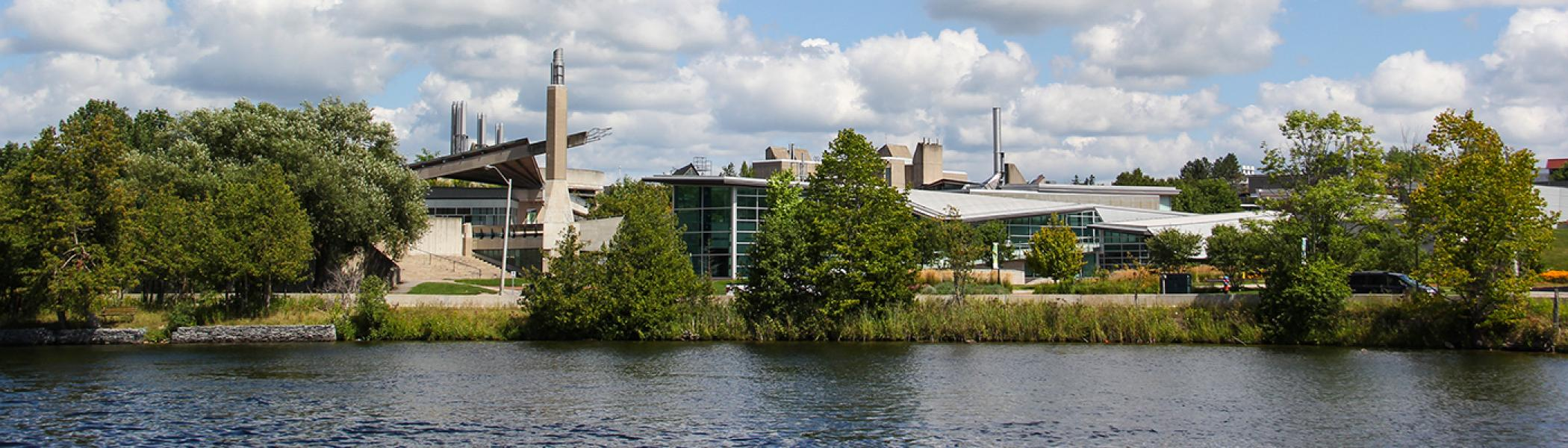 Exterior view of the Science complex from across the Otonabee river on a bright summer's day with blue sky and blue water