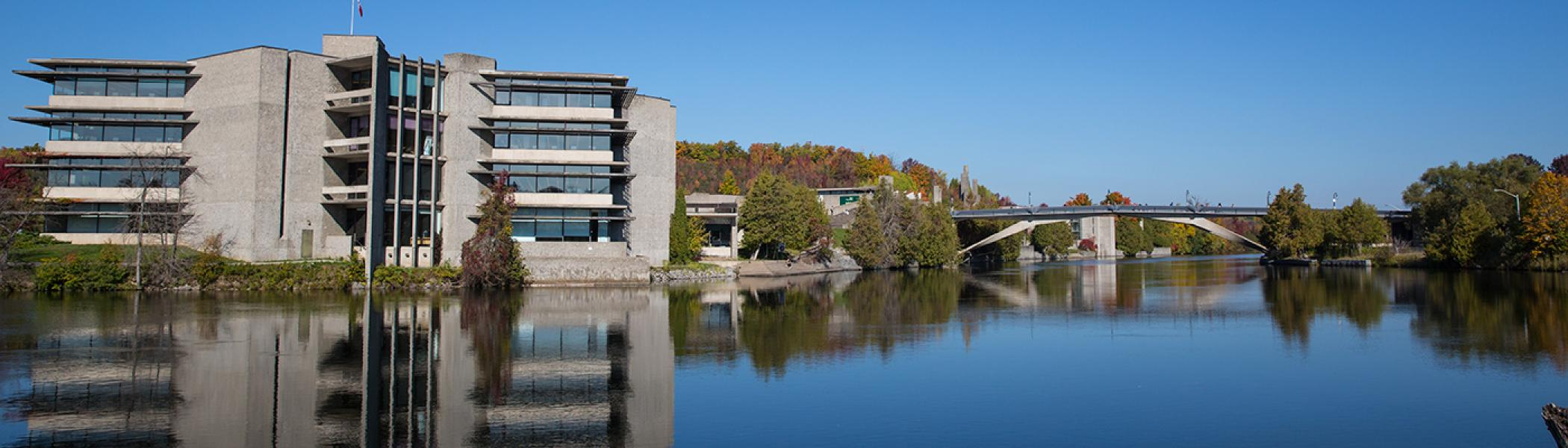 Exterior view of the Bata library and the Faryon bridge in the fall sun from across the otonabee river, looking North