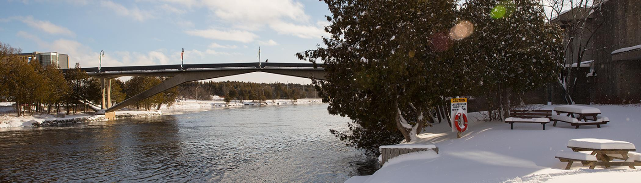 Exterior view of the Faryon bridge in the winter snow and sun from the Champlain College bank of the Otonabee river