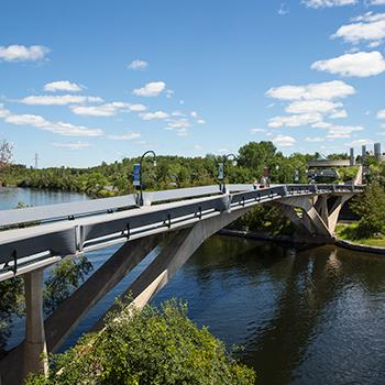 Summertime exterior view of the Faryon bridge with people waking across