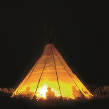 A traditional Tipi at night lit by the fire inside of it.