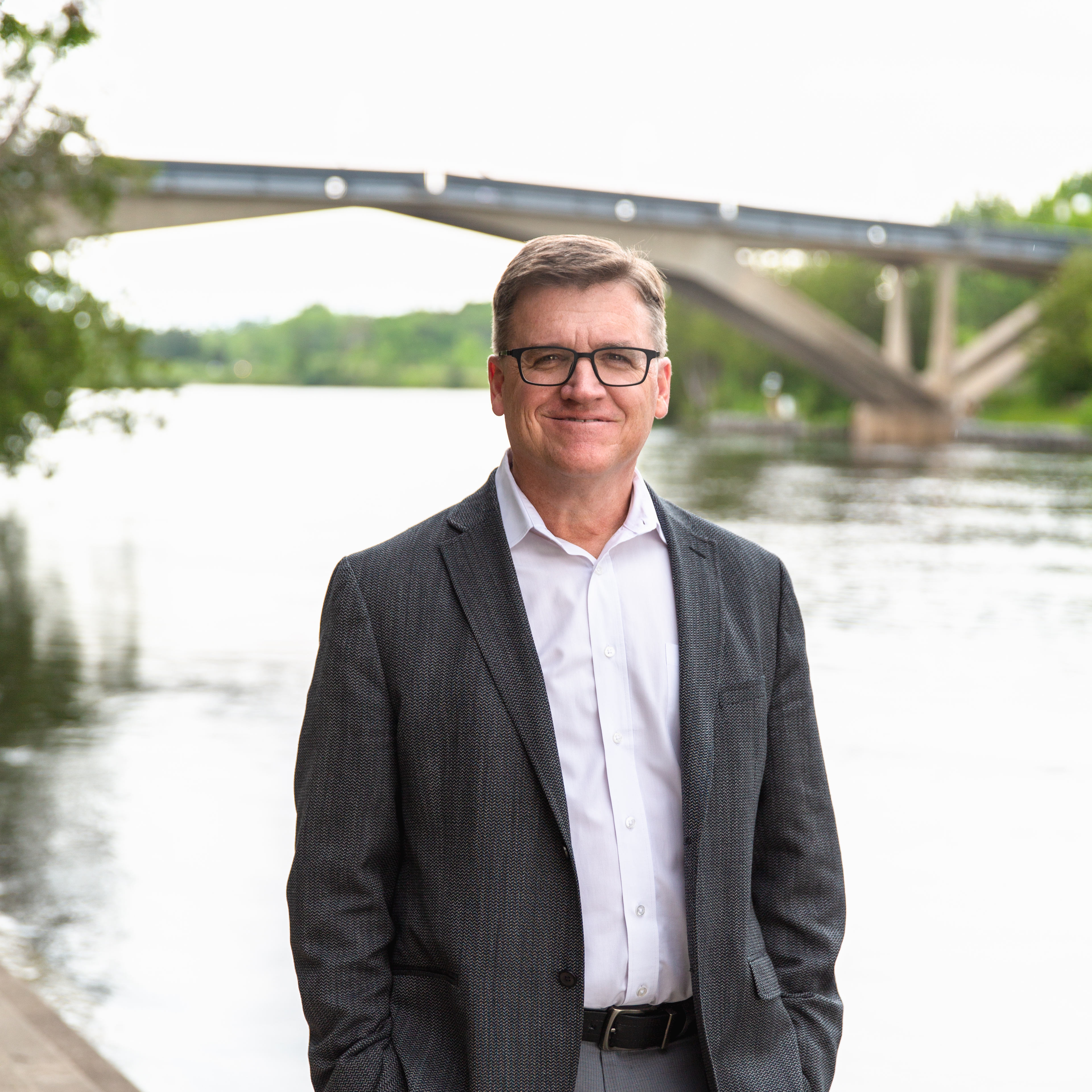 Vice President, Finance Administration, Kent Stringham stands beside the Otonabee river on the steps to Bata Library