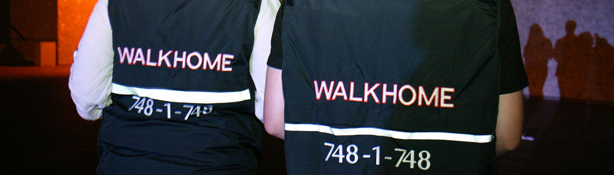 "two students with their backs facing the camera wearing ""Walk Home"" vests."