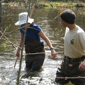 Two students in hip-waders in the water