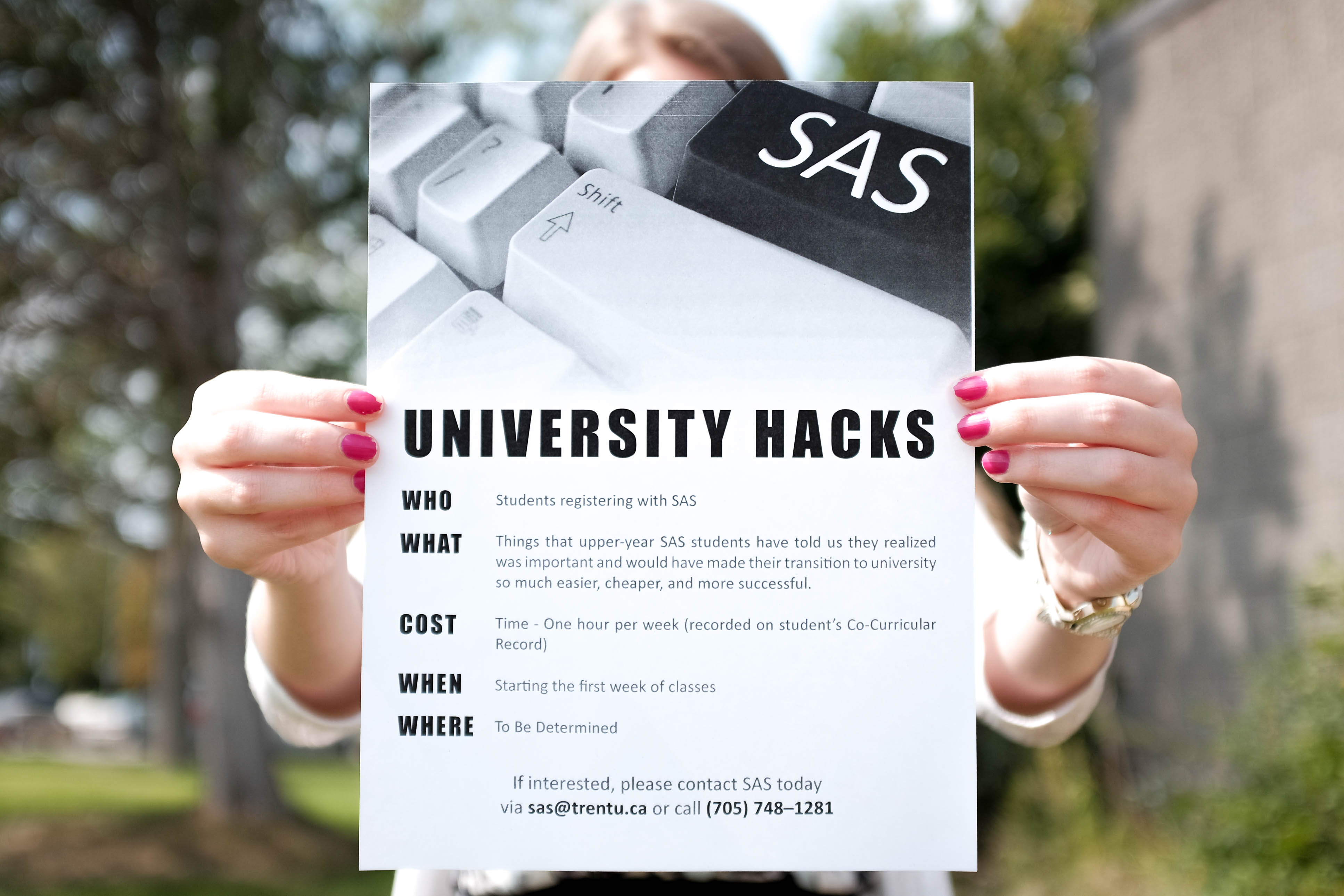 Student holding a promotional poster for University Hacks, poster is in prominent focus, only fingers are seen on the side of the poster.
