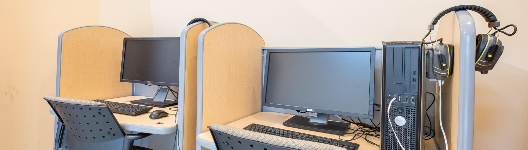 View of PC workstations with noise cancelling headphones.