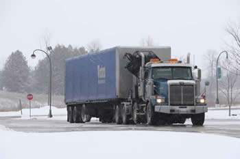 A large blue truck entering the Trent Symon's campus.