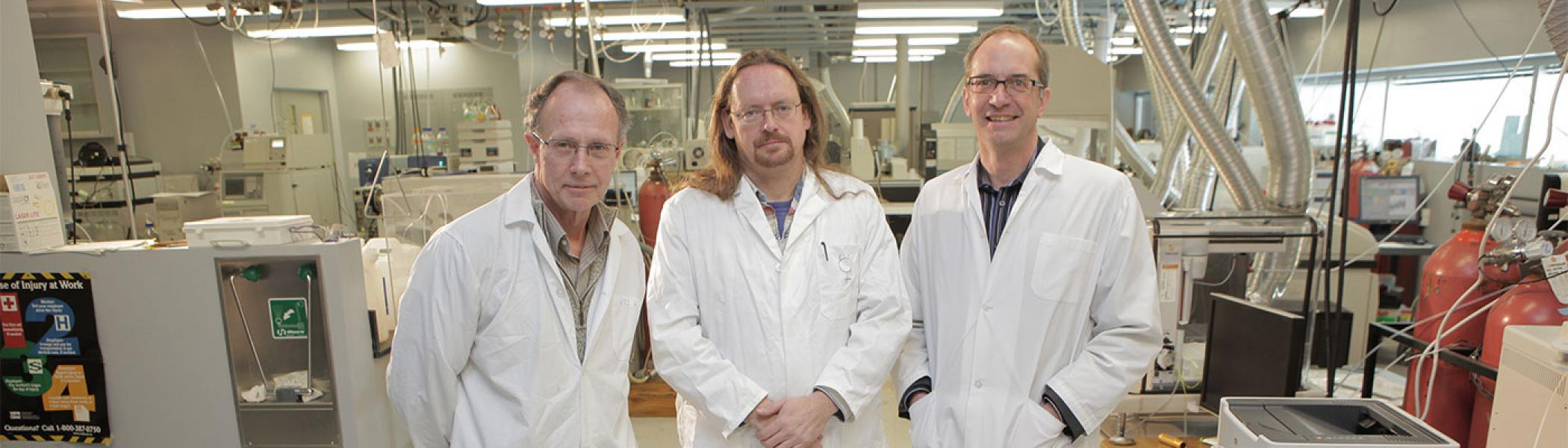 three individuals in white lab coats standing next to one another in the water quality centre