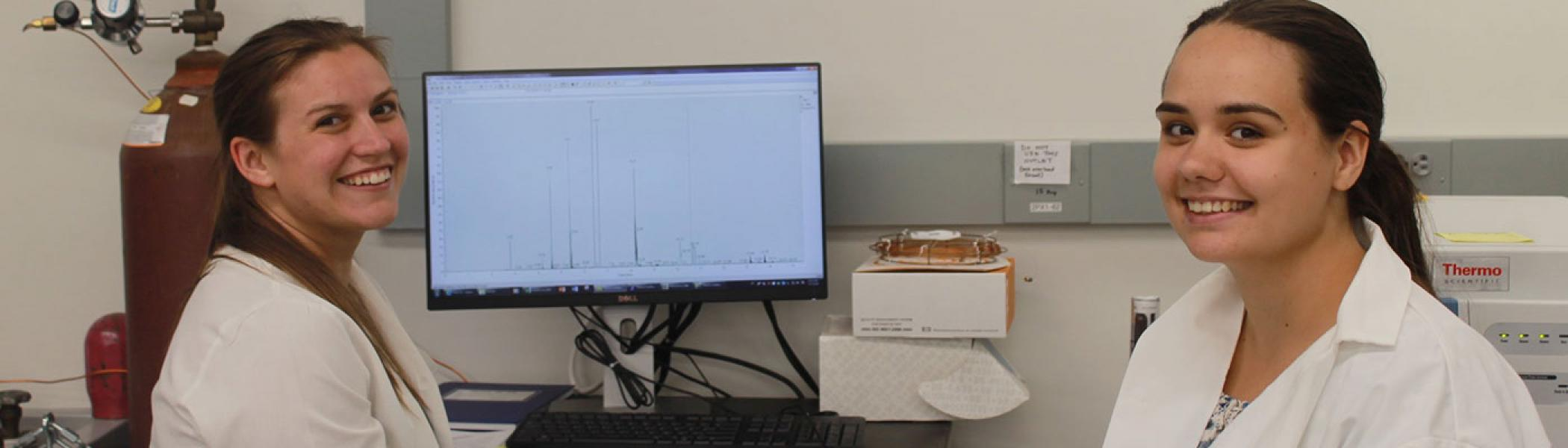 Two scientists analyzing data shown on a monitor.